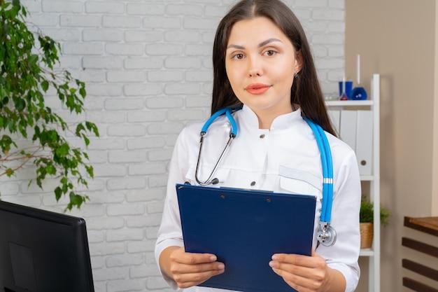Giovane medico donna bruna in piedi con appunti nel suo ufficio