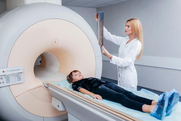 Giovane medico femmina che controlla un bambino nella stanza di risonanza magnetica