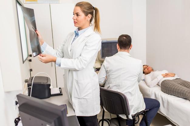 Giovane medico femmina guardando l'immagine a raggi x del paziente in ospedale
