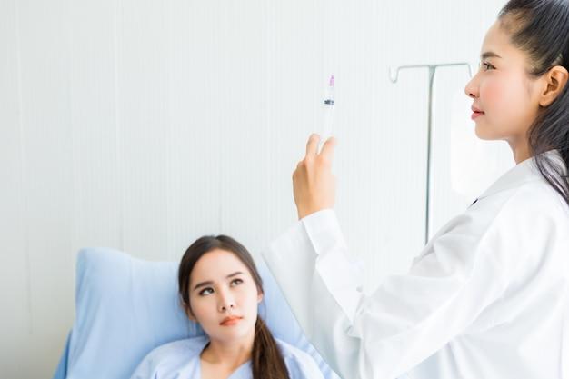 Giovane medico femminile asiatico con la siringa al giovane paziente femminile asiatico sul letto per una migliore guarigione nell'ospedale della stanza