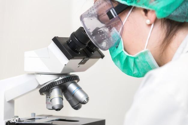 Giovane medico femminile che lavora con un microscopio in un laboratorio