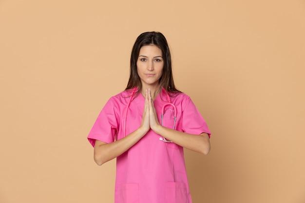 Giovane medico femminile con un'uniforme rosa che gesturing sopra la parete marrone
