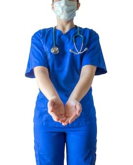 Giovane medico femminile di successo in un'uniforme medica blu e una maschera che mostra le mani vuote per aiutare