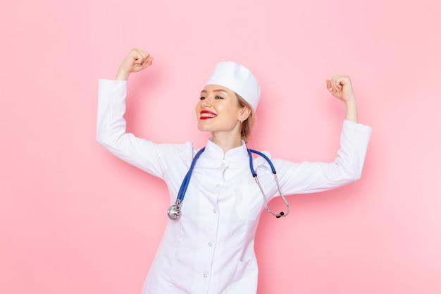 Giovane medico femminile di vista frontale in vestito bianco con lo stetoscopio blu che posa flettendo sul lavoro rosa dello spazio