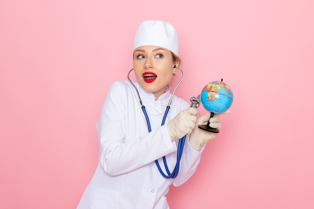 Giovane medico femminile di vista frontale in vestito medico bianco con lo stetoscopio blu che controlla il piccolo globo sull'ospedale medico della medicina dello spazio rosa