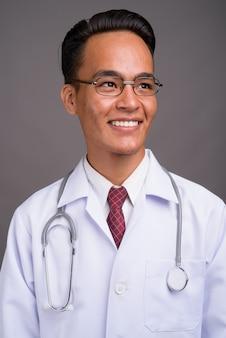 Giovane medico indiano bello dell'uomo contro la parete grigia