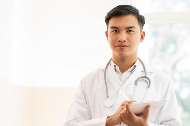 Giovane medico maschio che utilizza computer tablet con suite abito bianco indossando stetoscopio sul collo per la ricerca di informazioni sul trattamento di pazienti in ospedale o clinica, concetto medico sanitario