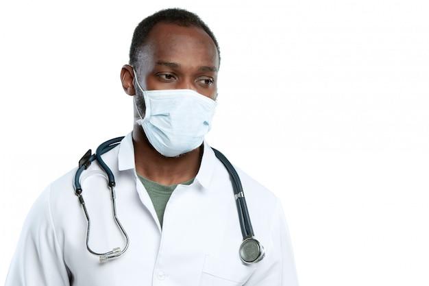 Giovane medico maschio con lo stetoscopio e la maschera di protezione isolati su bianco