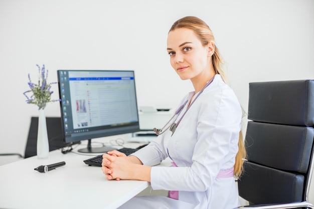 Giovane medico sorridente seduto alla scrivania su una sedia nera con le braccia incrociate