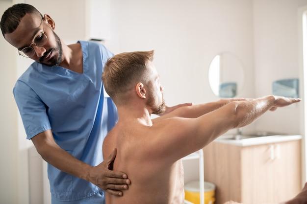 Giovane medico specialista di razza mista in uniforme che tocca la schiena del paziente seduto con le braccia tese davanti a lui
