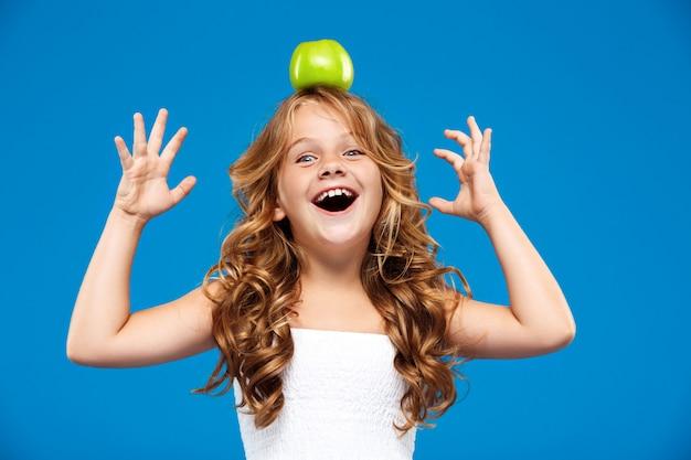 Giovane mela graziosa della tenuta della ragazza sulla testa sopra la parete blu