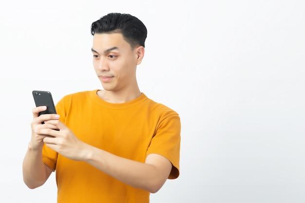 Giovane messaggio asiatico felice della lettura dell'uomo dallo smartphone con copyspace su bianco.