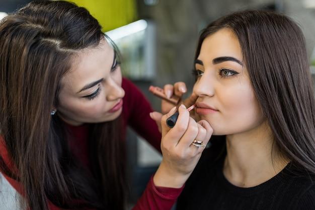 Giovane modella che prova un nuovo colore di rossetti durante la procedura di trucco