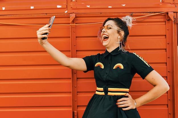 Giovane modella con look alternativo prendendo selfie e ridendo