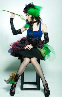 Giovane modella in abito carnevale con trucco creativo.