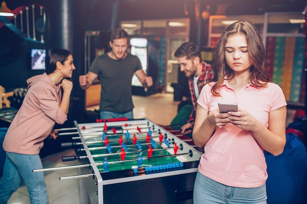 Giovane modella in camicia rosa tenere il telefono in mano. giovane squadra felice che gioca il gioco di calcio-balilla nella stanza di gioco. guy sta verso la donna.