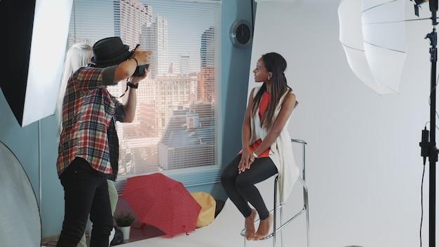 Giovane modello africano che posa sul seggiolone da bar durante il servizio fotografico