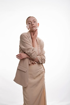Giovane modello biondo con trucco di arte che posa nel vestito di gonna beige