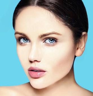 Giovane modello caucasico con trucco nudo che tocca la sua pelle pulita perfetta sull'azzurro