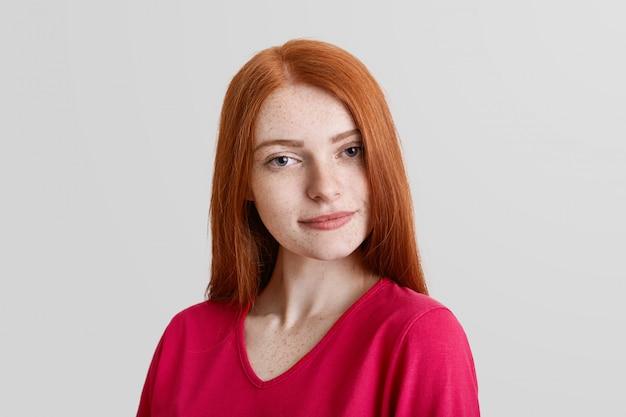 Giovane modello femminile lentigginoso di bell'aspetto, con le lentiggini sul viso, lunghi capelli lisci rossi, vestito con indifferenza, guarda con espressione misteriosa nella fotocamera, isolato su un muro bianco.