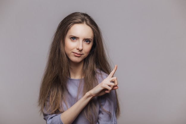 Giovane modello femminile sveglio con i capelli lunghi castana, punti allo spazio in bianco della copia della parete grigia