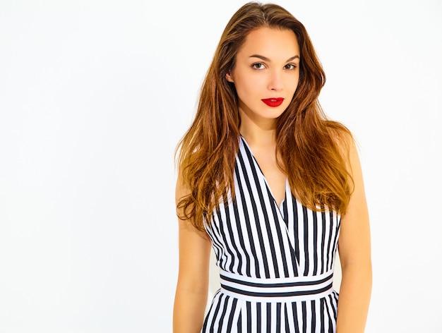 Giovane modello sorridente alla moda della donna in vestito a strisce di estate casuale con le labbra rosse, isolate