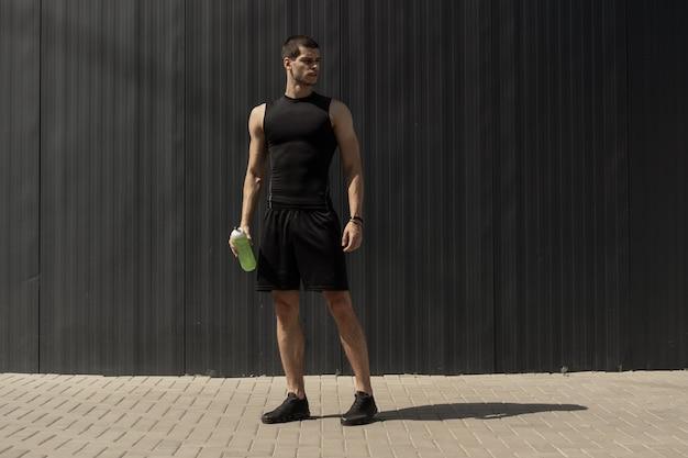 Giovane moderno atletico che posa su una parete metallica grigia