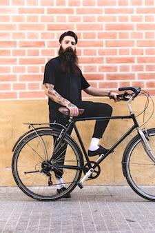 Giovane moderno che sta con la sua bicicletta contro il muro di mattoni