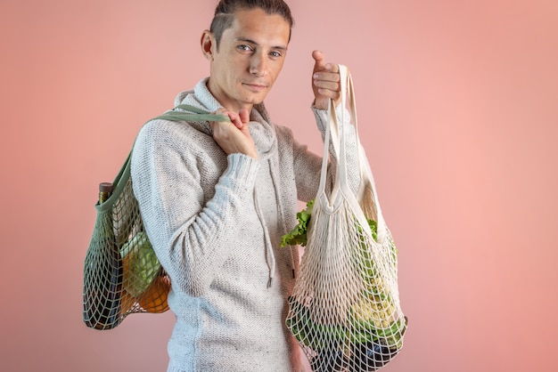 Giovane moderno che tiene le borse di una corda con gli acquisti