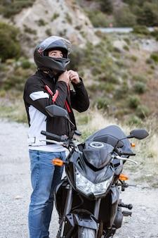 Giovane motociclista maschio che indossa il casco per guidare la sua moto
