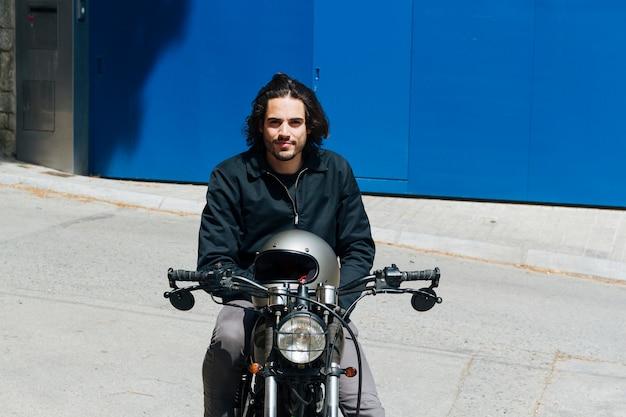 Giovane motociclista maschio sorridente che si siede sulla motocicletta che esamina macchina fotografica