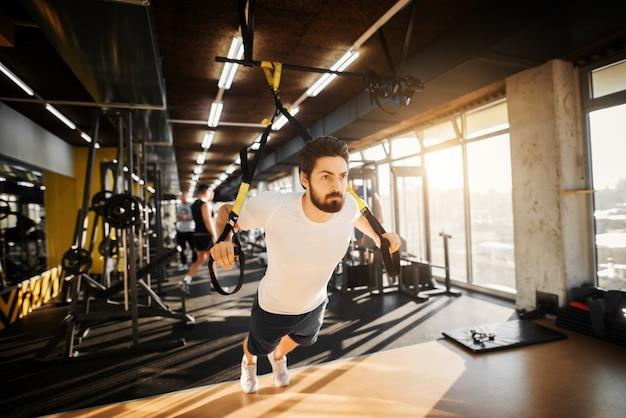 Giovane muscolare concentrato che si esercita con trx in palestra.