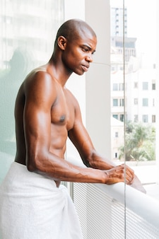 Giovane muscolare senza camicia bello con l'asciugamano che sta nel balcone