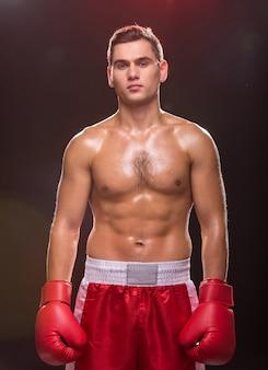 Giovane muscoloso con guantoni da boxe sul buio.