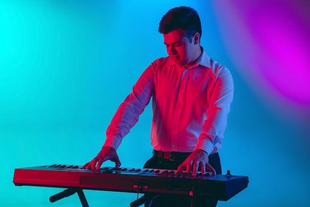 Giovane musicista caucasico, tastierista giocando su spazio sfumato in luce al neon. concetto di musica, hobby, festival