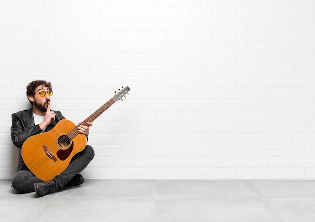 Giovane musicista che chiede silenzio e silenzio, gesticolando con il dito davanti alla bocca, dicendo shh o mantenendo un segreto con un concetto di chitarra, rock and roll
