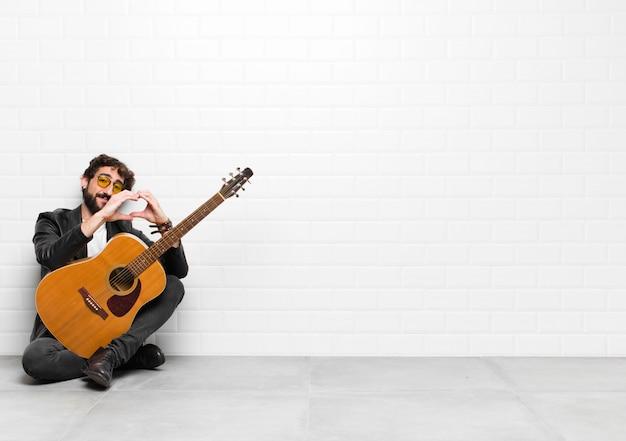 Giovane musicista che sorride e si sente felice, carino, romantico e innamorato, facendo a forma di cuore con entrambe le mani con un concetto di chitarra, rock and roll
