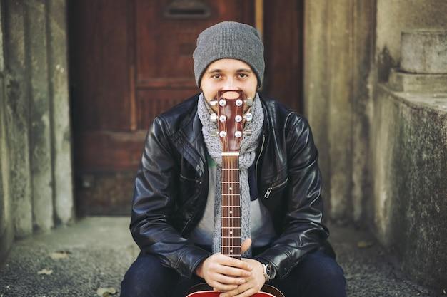Giovane musicista con la chitarra in città