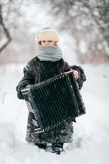 Giovane musicista felice. comic girl hold fisarmonica. il bambino adorabile in inverno divertente copre il ritratto all'aperto di stile di vita. strana bambina insolita che indossa giacca imbottita per adulti di grandi dimensioni. moda bambino in campagna