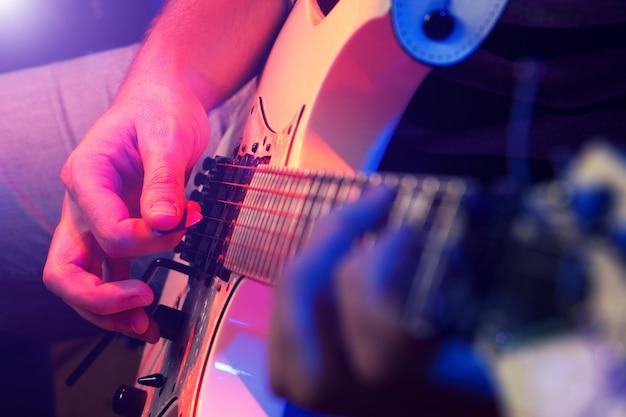 Giovane musicista maschio con una chitarra bianca
