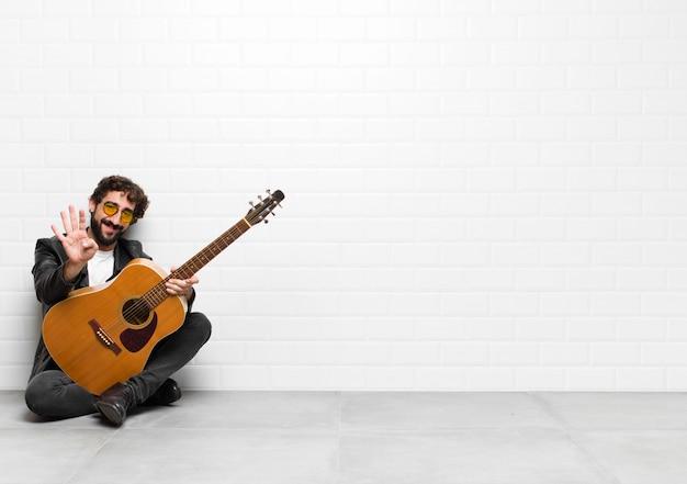 Giovane musicista uomo sorridente e guardando amichevole, mostrando il numero quattro o quarto con la mano in avanti, il conto alla rovescia con una chitarra, rock and roll concept