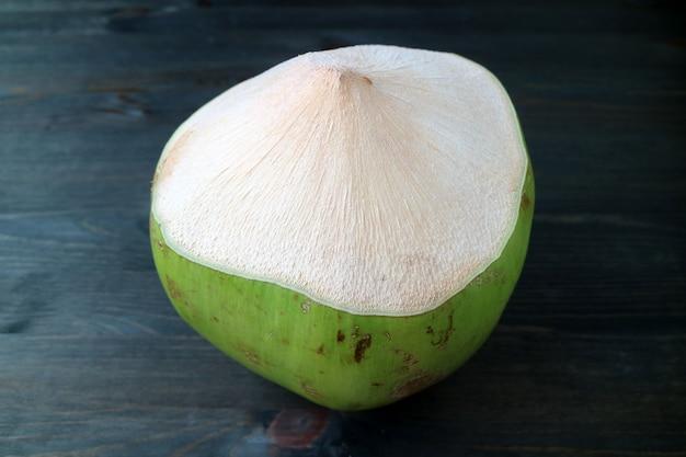 Giovane noce di cocco fresca pronta ad essere aperta per succo isolato sulla tavola di legno di colore scuro