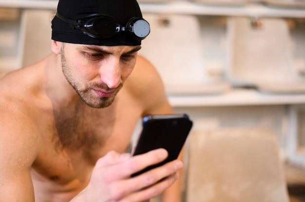 Giovane nuotatore maschio che per mezzo del telefono
