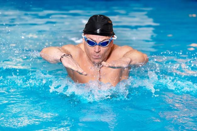 Giovane nuotatore muscolare in berretto nero in piscina, eseguendo il colpo di farfalla.