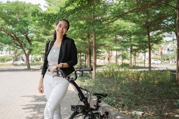 Giovane operaio asiatico sorridente della donna che sta con la sua bici pieghevole