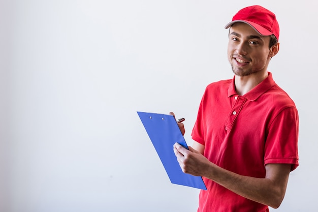 Giovane operaio bello nel sorridere rosso della protezione e della maglietta.