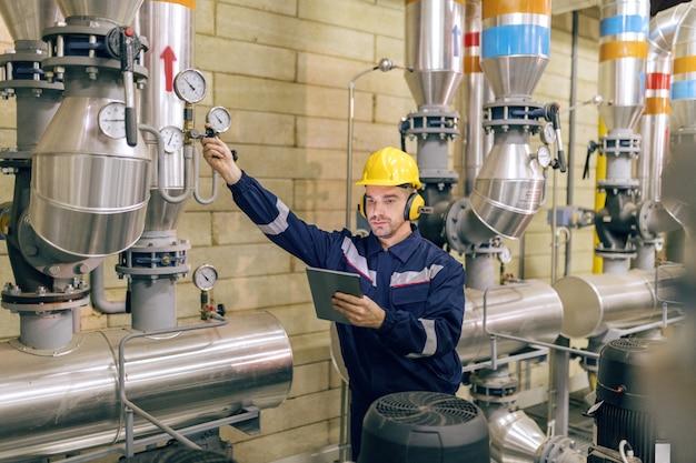 Giovane operaio caucasico in tuta protettiva stringendo la valvola e utilizzando la tavoletta mentre si trovava in impianto di riscaldamento.
