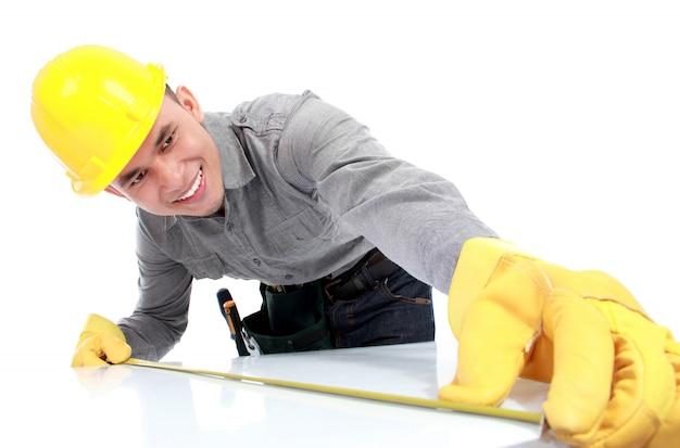 Giovane operaio con elmetto protettivo giallo