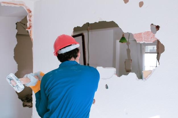 Giovane operaio con un casco di protezione rosso e indossa una tuta blu della caldaia. concetto di demolizione