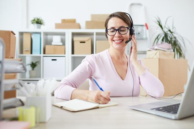 Giovane operatore amichevole di call center o negozio online che prende appunti